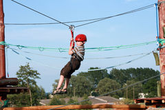 Child  in adventure playground. Portrait of young boy wearing helmet climbing. Child in a wooden abstacle course in adventure playground Royalty Free Stock Photography