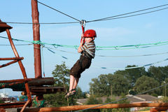 Child  in adventure playground. Portrait of young boy wearing helmet climbing. Child in a wooden abstacle course in adventure playground Royalty Free Stock Photos