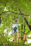 Child in a adventure playground. A boy in a helmet and safety equipment in adventure ropes park on the background of nature Stock Image