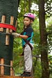Child in a adventure playground. A boy in a helmet and safety equipment in adventure ropes park on the background of nature Stock Images