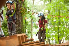 Child in a adventure playground. A boy in a helmet and safety equipment in adventure ropes park on the background of nature Royalty Free Stock Photography