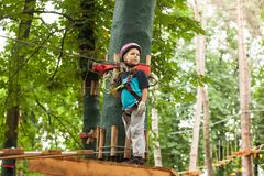 Child in a adventure playground. A boy in a helmet and safety equipment in adventure ropes park on the background of nature Stock Photo