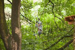 Child in a adventure playground. A boy in a helmet and safety equipment in adventure ropes park on the background of nature Stock Photography