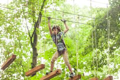Child in a adventure playground. A boy in a helmet and safety equipment in adventure ropes park on the background of nature Royalty Free Stock Images