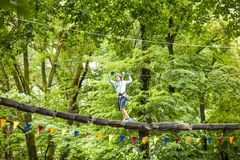 Child in a adventure playground. A boy in a helmet and safety equipment in adventure ropes park on the background of nature Royalty Free Stock Image