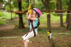Child in a adventure playground. Girl in a helmet and safety equipment in adventure ropes park get down in the end of way Royalty Free Stock Photo
