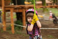 Child in a adventure playground. Girl in a helmet and safety equipment in adventure ropes park get down in the end of way Stock Photo
