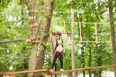 Child in a adventure playground. Teenage girl in a helmet and safety equipment in adventure ropes park on the background of nature Stock Photography