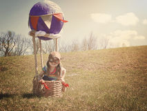 Child on Adventure Trip in Hot Air Balloon. A little girl is sitting in a hot air balloon pretending to be a pilot flying on a grass field for an imagination or royalty free stock photography