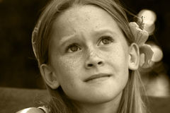 Child afraid. A white caucasian girl child with a worried expression on her face. Picture in sepia tone Royalty Free Stock Images