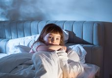 The child is afraid of lying in bed at night. Night terrors of the child. Fear of the dark. The baby on the bed at night. An empty space to insert text Stock Images