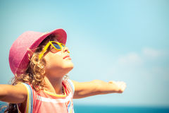 Child against blue sky background. Happy child against blue sky background. Summer vacation concept Royalty Free Stock Photo