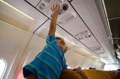 Child airline passenger pressing button stewardess Royalty Free Stock Photo