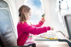 Child in airplane. Fly with family. Kids travel. Child in airplane. Kid in air plane sitting in window seat. Flight entertainment for kids. Traveling with young royalty free stock image