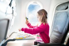 Child in airplane. Fly with family. Kids travel. Stock Photo