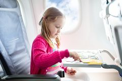Child in airplane. Fly with family. Kids travel. Child in airplane. Kid in air plane sitting in window seat. Flight entertainment for kids. Traveling with young stock photo