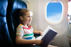 Child in airplane. Fly with family. Kids travel. Child in airplane. Kid with book in air plane sitting in window seat. Flight entertainment for kids. Traveling stock photo