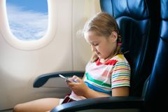 Child in airplane. Fly with family. Kids travel.pl. Child in airplane. Kid with mobile phone in air plane in window seat. Flight entertainment for kids royalty free stock image
