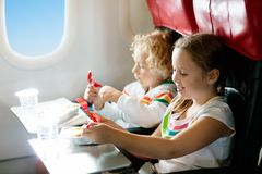 Child in airplane window seat. Kids flight meal. Children fly. Special inflight menu, food and drink for baby and kid. Girl and. Boy eating healthy lunch in royalty free stock image
