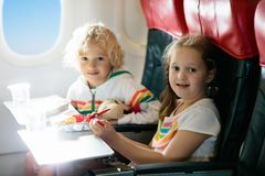 Child in airplane window seat. Kids flight meal. Children fly. Special inflight menu, food and drink for baby and kid. Girl and. Boy eating healthy lunch in stock images