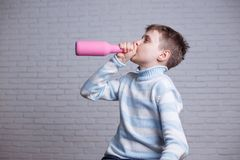 Child alcoholism. Boy drinking alcohol from a pink bottle. Hidin. G or masking an addiction stock photo