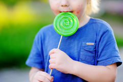 Child with allergic reaction eating big green lollipop. Unhealthy sweet food for young kids. Allergic rash dermatitis on toddler skin face Stock Photo