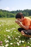 Child with an allergy to pollen while sneeze in the middle of th Royalty Free Stock Images