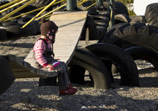 Child alone. Child sitting alone on a playground swing Stock Image