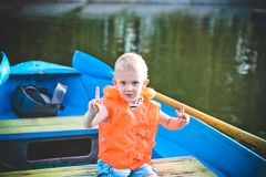 Child life jacket orange boat emotions anxiety. Child alone in a life jacket orange in a boat with emotions and anxiety royalty free stock images