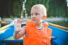 Child life jacket orange boat emotions anxiety. Child alone in a life jacket orange in a boat with emotions and anxiety stock photos