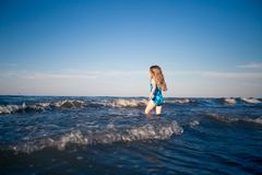 Child alone in the sea. Little girl going into the sea without parents. Ð¡hild care concept royalty free stock images
