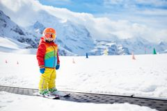 Child in alpine ski school with magic carpet lift and colorful training cones going downhill in the mountains on a sunny winter. Day. Little skier kid learning stock photos