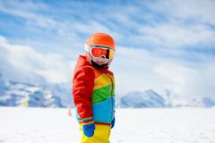 Child in alpine ski school with magic carpet lift and colorful training cones going downhill in the mountains on a sunny winter. Day. Little skier kid learning stock images