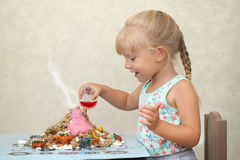 Child amused by a home made volcanoe.  stock photos