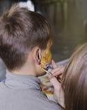 Child animator - artist`s hand draws face painting to little boy. Child animator, artist`s hand draws face painting to little boy Royalty Free Stock Photos