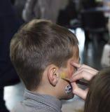 Child animator - artist`s hand draws face painting to little boy. Child animator, artist`s hand draws face painting to little boy Stock Photos