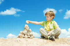 Child ans stones over blue sky Stock Photography