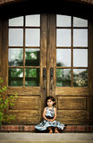 Child and antique door. Child sitting by an antique door Royalty Free Stock Images