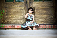 Child and antique door. Child sitting by an antique door Royalty Free Stock Photos