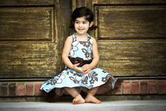 Child and antique door. Child sitting by an antique door Stock Photography