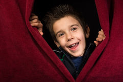 Child appearing beneath the curtain Stock Images