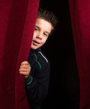 Child appearing beneath the curtain Royalty Free Stock Image