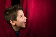 Child appearing beneath the curtain Stock Photo