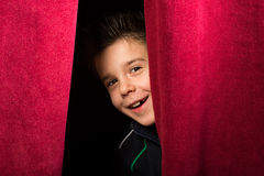 Child appearing beneath the curtain Stock Photography