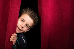 Child appearing beneath the curtain Royalty Free Stock Photo