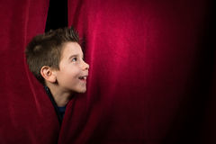 Child appearing beneath the curtain Royalty Free Stock Photography