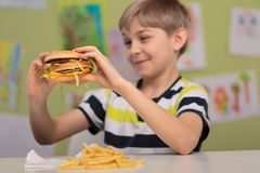 Child with appetite for hamburger. Photo of child with appetite for fat and caloric hamburger Royalty Free Stock Image