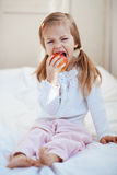 Child with apple. Casual portrait of cute child with apple in bed Stock Image