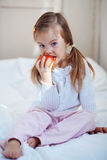Child with apple. Casual portrait of cute child with apple in bed Stock Photography