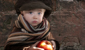 Child with apple. Little sad child with red apple, copy space on grange wall background Stock Photography